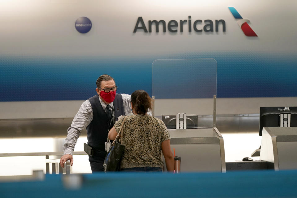 American Airlines ticket agent Henry Gemdron, left, works with a customer at Miami International Airport during the coronavirus pandemic, Wednesday, Sept. 30, 2020, in Miami. The airline industry has been decimated by the pandemic. The Payroll Support Program given to the airlines as part of the CARES Act runs out Thursday. (AP Photo/Lynne Sladky)