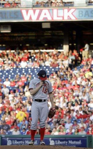 Washington Nationals starting pitcher Dan Haren wipes his face after walking Philadelphia Phillies' Darin Ruf with the bases loaded to score Jimmy Rollins during the first inning of a baseball game, Monday, July 8, 2013, in Philadelphia. (AP Photo/Matt Slocum)