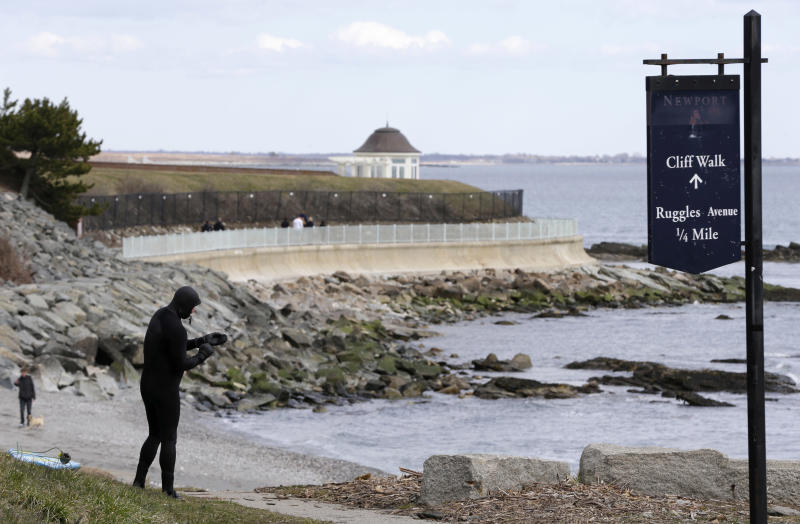 FILE - In this Wednesday, March 27, 2013 photo surfer Dave Livingston, of Newport, R.I., left, removes his gloves while standing near a portion of the Cliff Walk, in Newport, R.I. The Cliff Walk is one of a number of free attractions in Rhode Island that can be visited in the Summer. (AP Photo/Steven Senne, File)