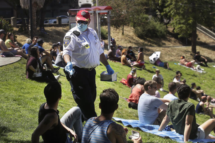 """FILE - San Francisco Police Auxiliary Law Enforcement Response Team (ALERT) volunteer David Flynn offers face masks to help prevent the spread of the coronavirus at Dolores Park in San Francisco, Sunday, May 24, 2020. California is creating roving """"strike teams"""" drawn from seven state agencies that will enforce state guidelines designed to slow the spread of the coronavirus, Gov. Gavin Newsom said Wednesday, July, 1, 2020. The teams include representatives from the California Highway Patrol; the Division of Occupational Safety and Health, known as CalOSHA; the Department of Alcohol Beverage Control; the Board of Barbering & Cosmetology; the departments of Business Oversight and Consumer Affairs. (AP Photo/Jeff Chiu, File)"""