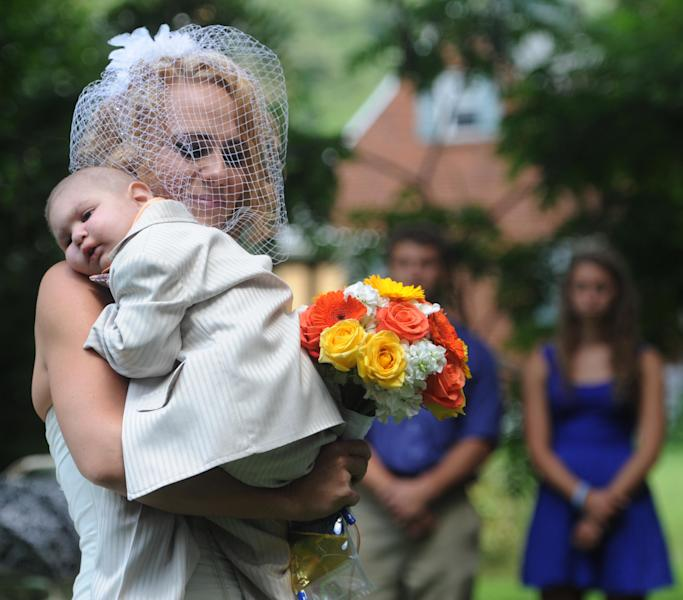 Christine Swidorsky carries her son and the couple's best man, Logan Stevenson, 2, down the aisle to her husband-to-be Sean Stevenson during the wedding ceremony on Saturday, Aug. 3, 2013 in Jeannette, Pa. Logan stood with his grandmother, Debbie Stevenson, during a 12-minute ceremony uniting Logan's mother and his father. The boy has leukemia and other complications. The Stevensons abandoned an original wedding date of July 2014 after learning from doctors late last month that their son had two to three weeks to live. The couple wanted Logan to see them marry and to be part of family photos. Logan, who was born Oct. 22, 2010, was diagnosed shortly after his first birthday with acute myeloid leukemia. He has Fanconi anemia, a rare disease that often leads to cancer. (AP Photo/Tribune Review, Eric Schmadel) PITTSBURGH OUT