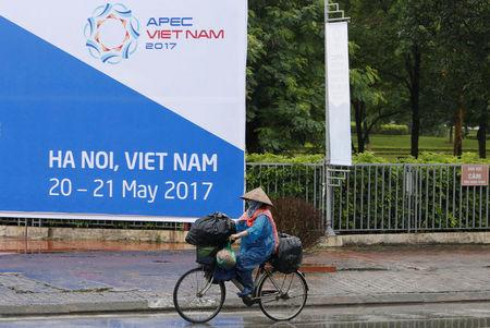 A woman bikes past a banner welcoming APEC trade ministers for a meeting in Hanoi, Vietnam May 19, 2017. REUTERS/Kham