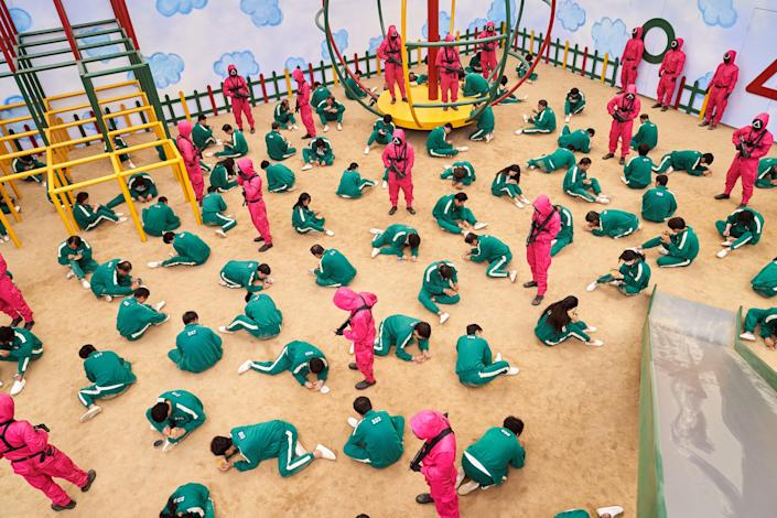 Contestants in green jump suits on the floor in a frame from the show Squid Game