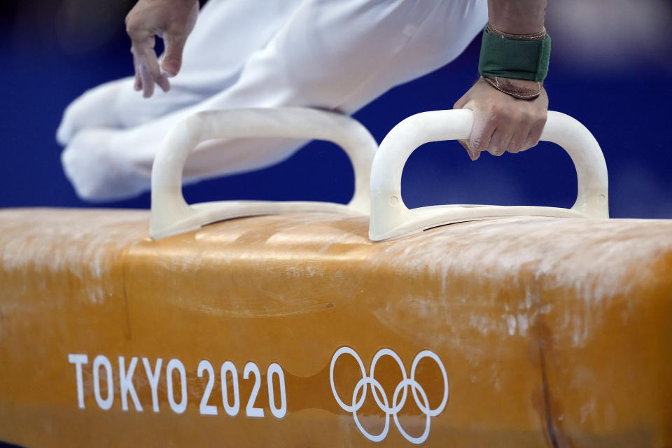 FILE - In this Aug. 1, 2021, file photo, David Belyavskiy, of the Russian Olympic Committee, performs on the pommel horse during the artistic gymnastics men's apparatus final at the 2020 Summer Olympics in Tokyo, Japan. At the Games, men swing around a leather-covered block with handles called a pommel horse, that in early iterations roughly mimicked the size and shape of the actual animal. (AP Photo/Ashley Landis, File)
