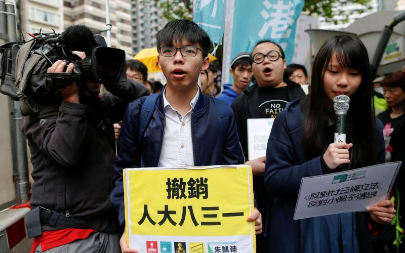 Democracy activist Joshua Wong leads a protest in Hong Kong as the election is held on Sunday - Credit: Reuters