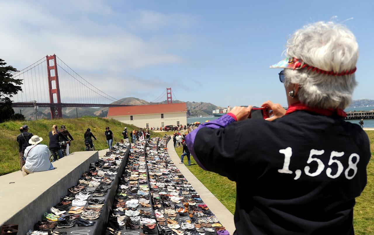 Roberta McLauglin photographs an exhibit of shoes in remembrance of people who have jumped from the Golden Gate Bridge during a commemoration of the bridge's 75th anniversary on Sunday, May 27, 2012, in San Francisco. The Bridge Rail Foundation, which advocates for a safety net along the span to prevent suicides, estimates approximately 1,558 people have died after jumping since the bridge opened. (AP Photo/Noah Berger)
