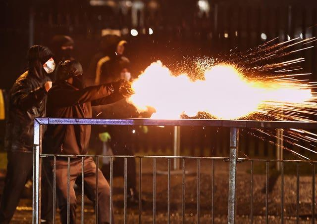 Youths discharge fireworks at the PSNI on the Springfield Road