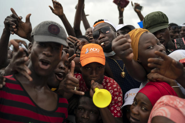 Supporters cheer for Ivory Coast President Alassane Ouattara before his arrival at a rally in Anyama, in the outskirts of Abidjan, Ivory Coast, Wednesday, Oct. 28, 2020. Ouattara, who first came to power after the 2010 disputed election whose aftermath left more than 3,000 people dead, is now seeking a third term in office. The candidate maintains that he can serve a third term because of changes to the country's constitution, though his opponents consider his candidacy illegal. (AP Photo/Leo Correa)