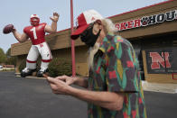 A Nebraska fan stops to take a picture of a giant inflatable football player standing in front of the Husker Hounds sports apparel store in Omaha, Neb., Wednesday, Sept. 16, 2020. It was put up Wednesday after the Big Ten conference changed course Wednesday and said it plans to begin its NCAA college football season the weekend of Oct. 23-24. Each team will have an eight-game schedule. (AP Photo/Nati Harnik)