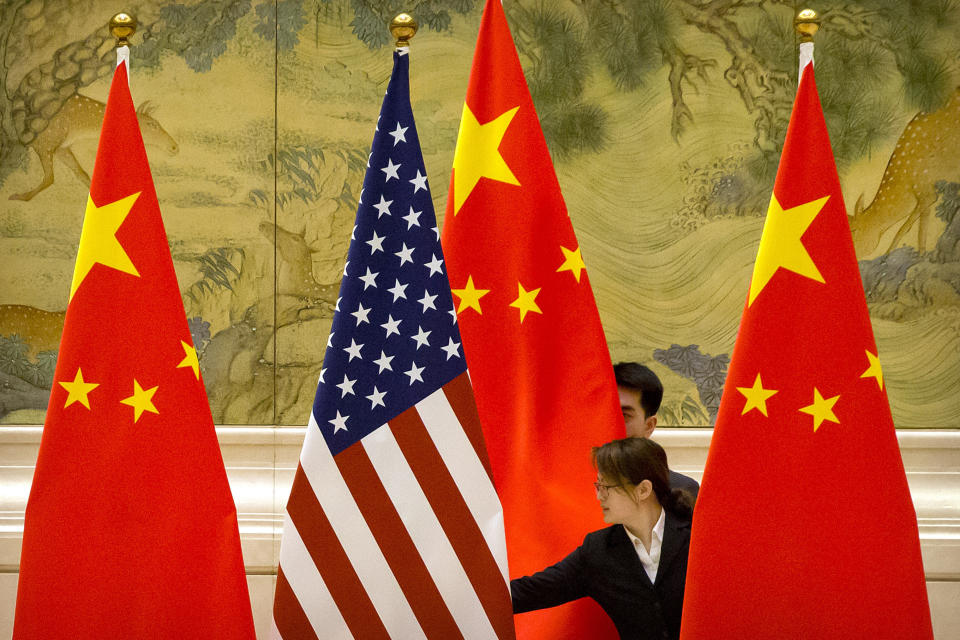 FILE - In this Feb. 14, 2019, file photo, Chinese staffers adjust the U.S. and Chinese flags before the opening session of trade negotiations between U.S. and Chinese trade representatives at the Diaoyutai State Guesthouse in Beijing. In a relationship as fraught as America's and China's, just an agreement that talks were productive was a sign of progress. Nine months into Joe Biden's presidency, the two sides finally appear to be trying to ease tensions that date from the Trump administration — though U.S. complaints about Chinese policies on trade, Taiwan and other issues are little diminished. (AP Photo/Mark Schiefelbein, File)