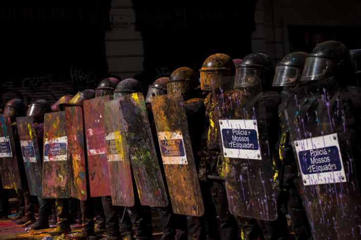 Catalan police officers cordon off the street to stop pro independence demonstrators on their way to meet demonstrations by members and supporters of National Police and Guardia Civil, as coloured powder is seen thrown by protesters, in Barcelona on Saturday, Sept. 29, 2018. (AP Photo/Emilio Morenatti)