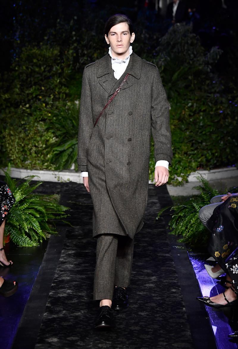 Model wears a tweed coat, collared shirt, and trousers from the new Erdem x H&M collection. (Photo: Getty)