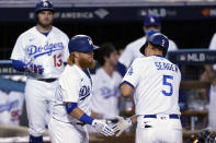 Los Angeles Dodgers' Corey Seager (5) is met at home plate by Justin Turner after Seager's solo home run against the Milwaukee Brewers during the seventh inning in Game 1 of a National League wild-card baseball series Wednesday, Sept. 30, 2020, in Los Angeles. (AP Photo/Ashley Landis)