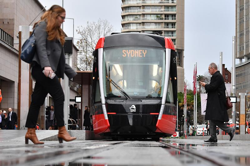 A ginger-haired woman and man cross the tracks at Circular Quay.