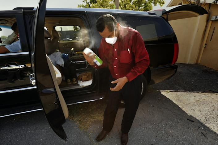 """Juan Lopez sprays himself down with disinfectant after moving a body. <span class=""""copyright"""">(Carolyn Cole / Los Angeles Times)</span>"""