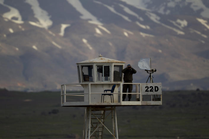 A U.N. peacekeeper from the UNDOF force looks through binoculars as he guards on a watch tower at the Quneitra Crossing between Syria and the Israeli-controlled Golan Heights, Friday, March 8, 2013. Syrian rebels who seized 21 Filipino U.N. peacekeepers in the Golan Heights want the Red Cross to escort them out of the area because of fighting with Syrian government forces, the Philippine military said Friday. The 21 peacekeepers were seized Wednesday near the Syrian village of Jamlah, just a mile from the Israeli-controlled Golan Heights in an area where the U.N. force had patrolled a cease-fire line between Israel and Syria without incident for nearly four decades. (AP Photo/Ariel Schalit)