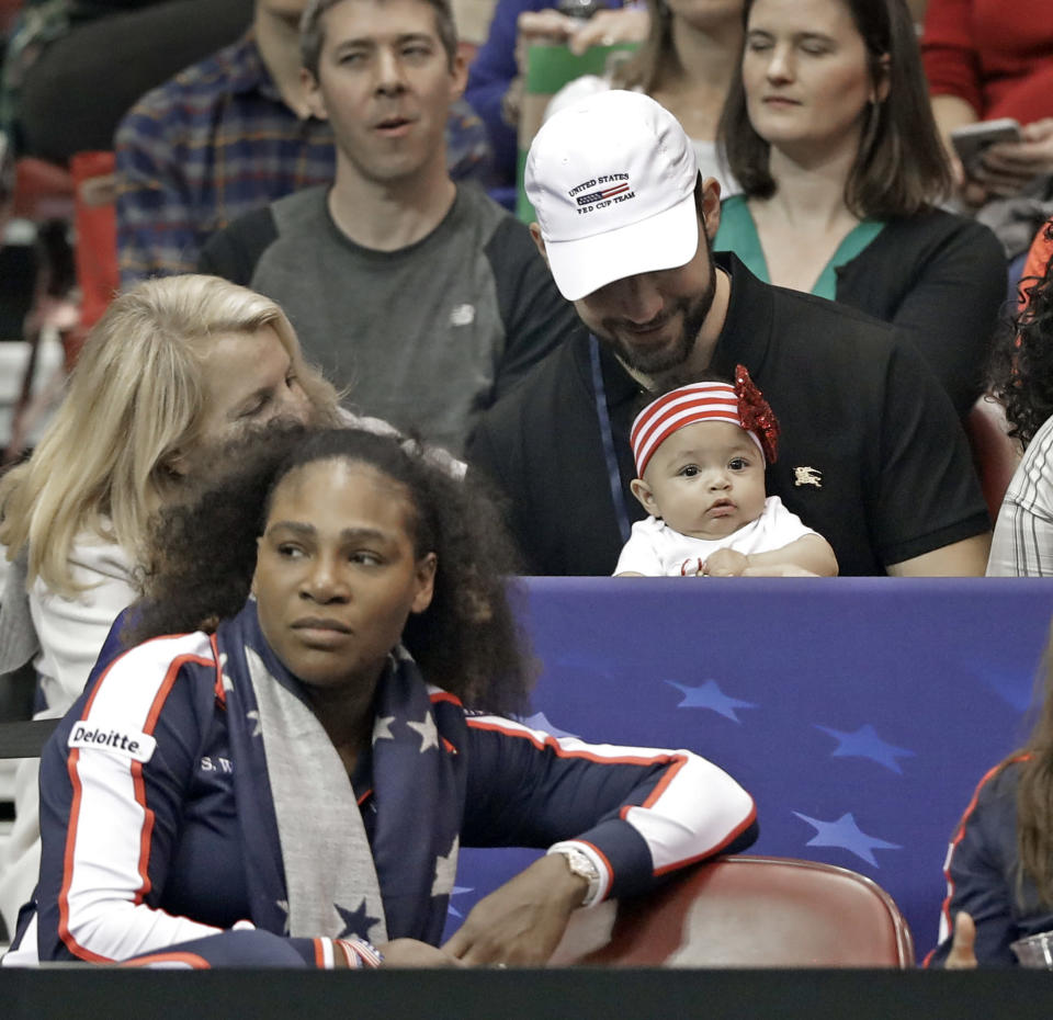 Serena Williams, left, watches the action with husband Alexis Ohanian, top right, and their baby, Alexis Olympia Ohanian Jr. during a match in the first round of Fed Cup tennis competition in Asheville, N.C., in February. (AP)