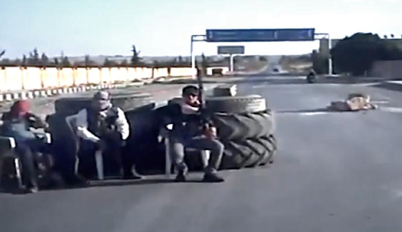 In this image taken from video obtained Wednesday, Sept. 19, 2012 from the Ugarit News, which has been authenticated based on its contents and other AP reporting, Free Syrian Army soldiers sit at a check point in Ain al-Arous town in Raqqa, Syria on Tuesday, Sept. 18, 2012. (AP Photo/Ugarit News via AP video)