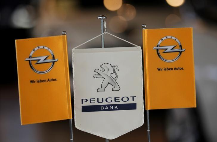 The logo of German General Motors daughter Opel and the bank of French car maker Peugeot are seen at a Opel and Peugeot dealership in Leverkusen