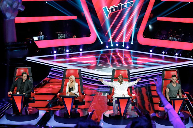 "This June 2012 photo released by NBC shows mentors, from left, Blake Shelton, Christina Aguilera, Cee Lo Green and Adam Levine on the set of ""The Voice,"" in Los Angeles. The contest between ""The Voice"" and ""The X Factor"" is escalating after NBC scheduled its ""Voice"" against Wednesday's second-season debut of Fox's ""X Factor."" (AP Photo/NBC, Tyler Golden)"