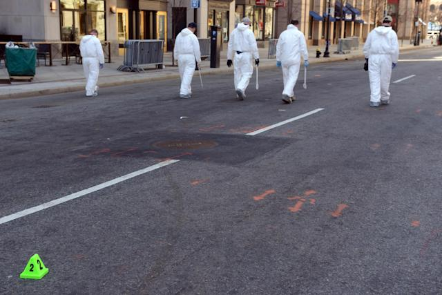 BOSTON - APRIL 17: FBI crime scene investigators sweep up Boylston Street after placing an evidence marker down just past Berkeley Street April 17, 2013 in Boston, Massachusetts. Investigators continue to work the scene of two bomb explosions at the finish line of the marathon that killed 3 people and injured over one hundred more. (Photo by Darren McCollester/Getty Images)
