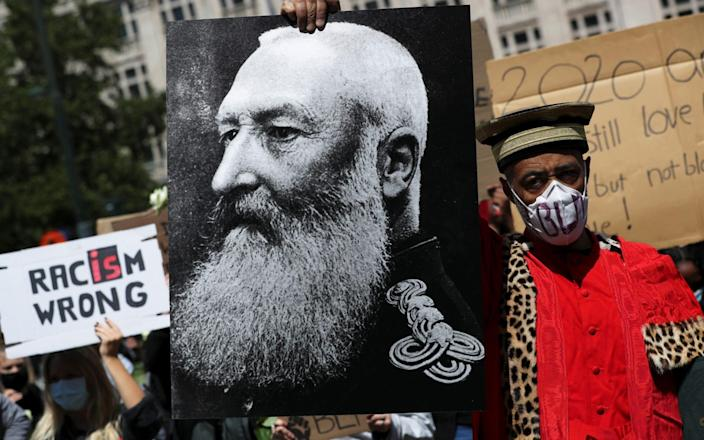 A Black Lives Matter protester holds a portrait of Leopold II at a demonstration in Brussels this month. - Yves Herman/Reuters