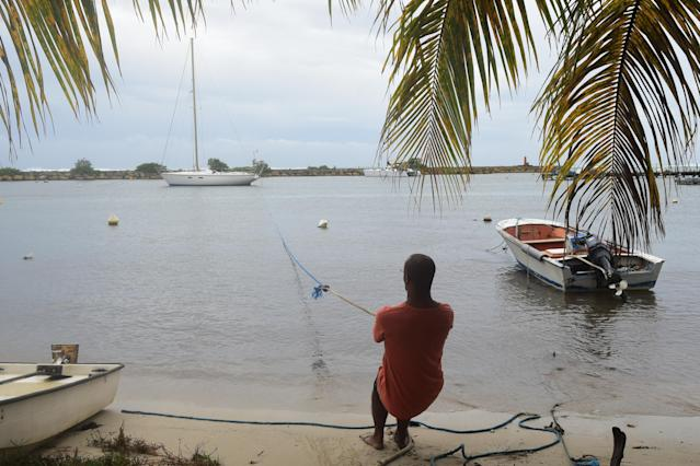 <p>A man pulls in a boat ahead of Hurricane Maria in the Galbas area of Sainte-Anne on the French Caribbean island of Guadeloupe, early Monday, Sept. 18, 2017. (Photo: Dominique Chomereau-Lamotte/AP) </p>