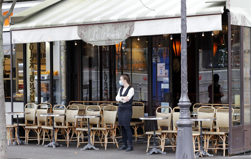 PARIS, FRANCE - OCTOBER 22: A waitress wearing a protective face mask waits for customers in front of an empty restaurant terrace near Notre-Dame Cathedral during the coronavirus outbreak on October 22, 2020 in Paris, France. In the absence of tourists due to the coronavirus pandemic (COVID 19) and measures taken by the French government to curb the disease, many bars, restaurants and souvenir shops are empty in tourist sites in the capital. (Photo by Chesnot/Getty Images)