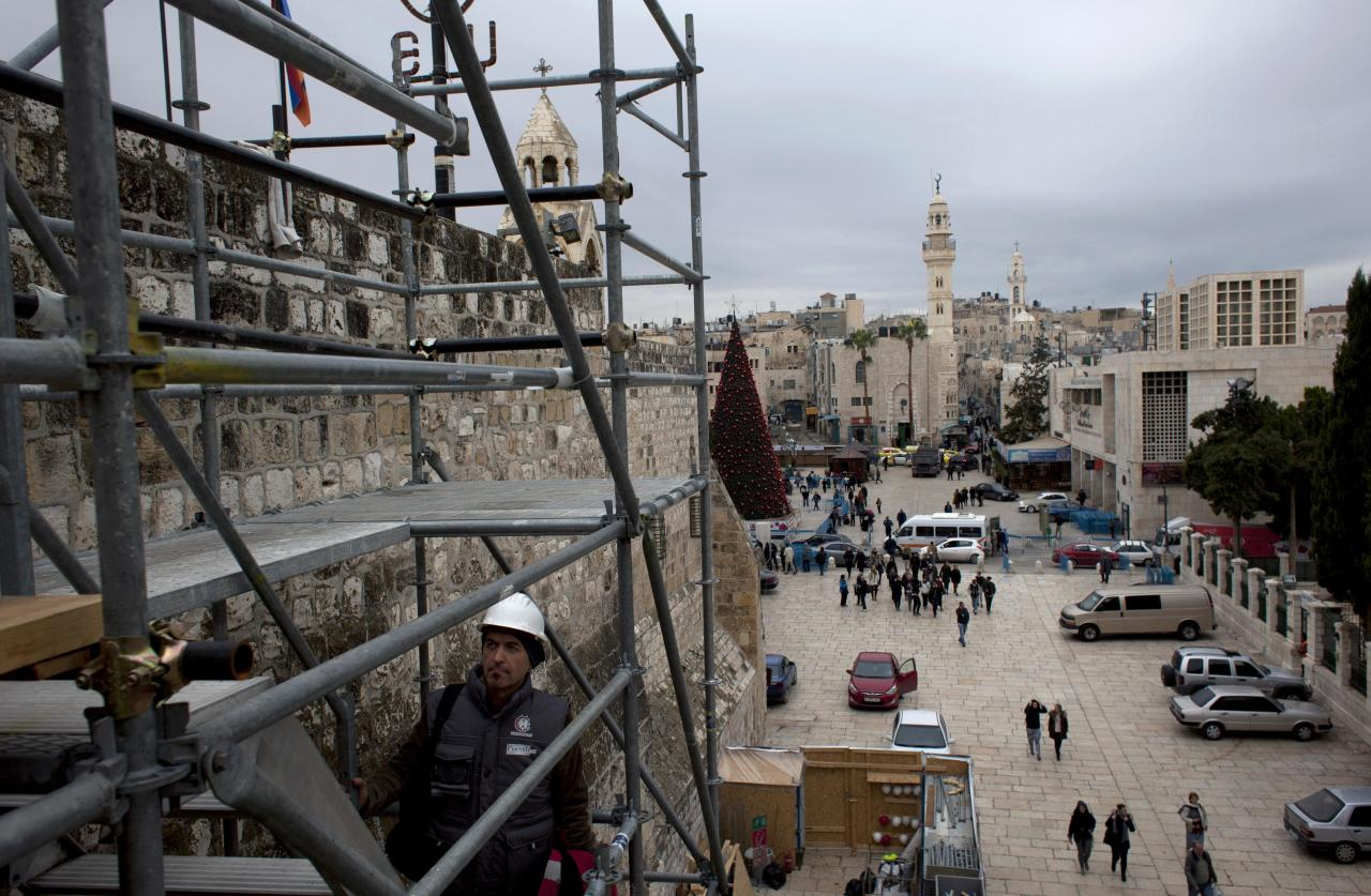 In this Tuesday Dec. 10, 2013 photograph, tourists walk around the Church of the Nativity in the West Bank city of Bethlehem. To visitors arriving in Bethlehem for Christmas this year the Nativity Church will look different. Wrapped in scaffolding, the basilica is having a much-needed facelift after 600 years. Last year it has been included in UNESCO's list of endangered World Heritage sites. (AP Photo/Nasser Nasser)