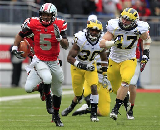 Ohio State quarterback Braxton Miller, left, breaks away from Michigan defenders Thomas Gordon, center, and Jake Ryan during the third quarter of an NCAA college football game Saturday, Nov. 24, 2012, in Columbus, Ohio. Ohio State beat Michigan 26-21. (AP Photo/Jay LaPrete)