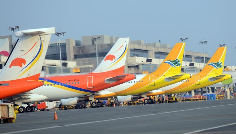 Aircraft of Philippine's largest budget carrier Cebu pacific (R) and Airphilippines (L), a subsidiary of flag carrier Philippine airlines, are parked at terminal 3 of the international airport in Manila on October 17, 2012