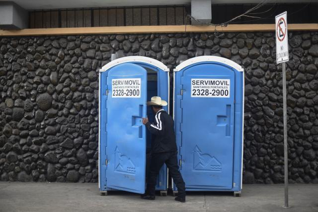 <p>A man enters a <em>toilet movil</em> in Guatemala City, Guatemala. (Photo: Ohan Ordonez/AFP/Getty Images) </p>