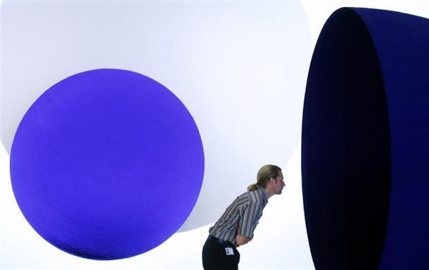 A member of Tate staff looks at Anish Kapoor's Untitled 1990 work winner of the Turner prize in 1991, part of the Turner Prize : A Retrospective exhibition, at the Tate Britain Gallery in London October 1, 2007.