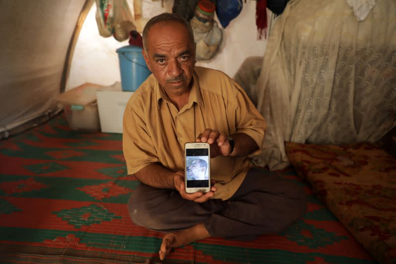 Khaled Mohamed al-Ahmed, 52, displays a picture of his deceased nephew in Idlib