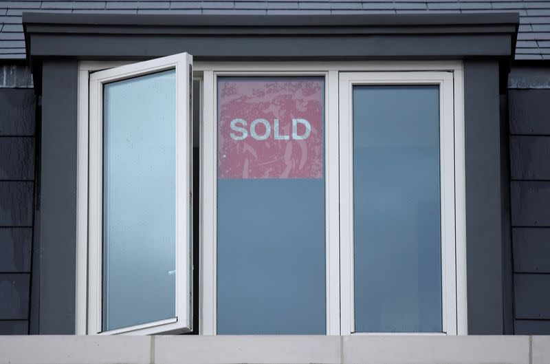FILE PHOTO: Property sold signs are seen on windows of a group of newly built houses in west London