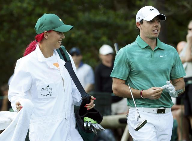 Tennis player Caroline Wozniacki of Denmark (L) works as the caddie for her boyfriend, Northern Ireland's Rory McIlroy, during the Par 3 Contest ahead of the Masters golf tournament at the Augusta National Golf Club in Augusta, Georgia April 9, 2014. REUTERS/Mike Segar (UNITED STATES - Tags: SPORT GOLF SPORT TENNIS)