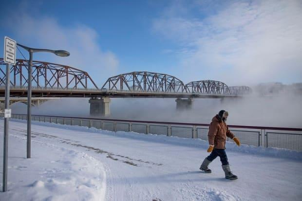 A pedestrian walks by River Landing beside the South Saskatchewan River during an extreme cold warning in Saskatoon on Jan. 25.