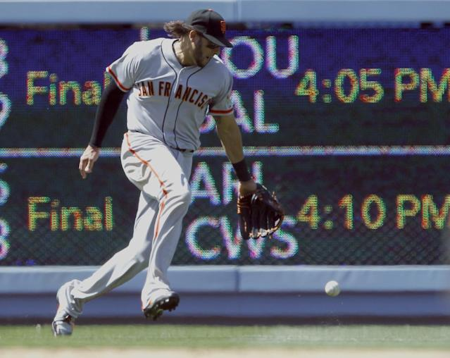 The ball drops next to San Francisco Giants left fielder Michael Morse for a single hit by Los Angeles Dodgers' Yasiel Puig in the sixth inning of a baseball game on Saturday, May 10, 2014, in Los Angeles. (AP Photo/Alex Gallardo)