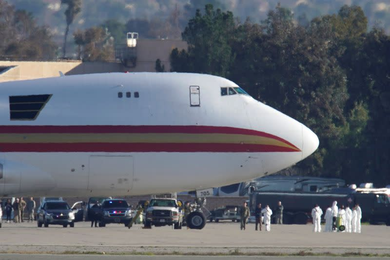 Personnel in protective clothing approach an aircraft at March Air Reserve Base in Riverside County