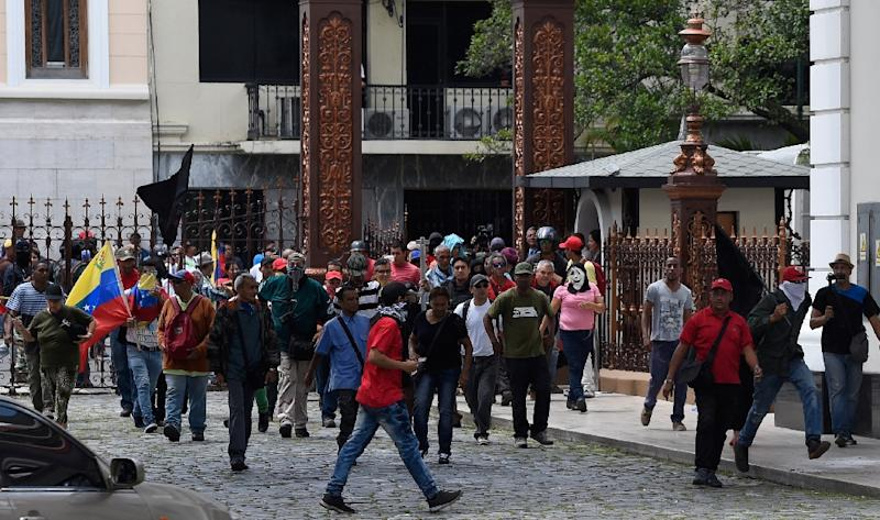 Stick-wielding supporters of Venezuelan President Nicolas Maduro broke through the front gate of the National Assembly building and set off fireworks in the interior gardens