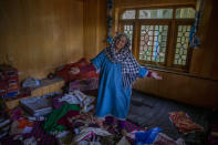 A Kashmiri woman stands amid belongings in a house allegedly ransacked by security forces after suspected militants killed a policeman in Beerwah area, Indian controlled Kashmir, Friday, Feb. 19, 2021. Anti-India rebels in Indian-controlled Kashmir killed two police officers in an attack Friday in the disputed region's main city, officials said. Elsewhere in the Himalayan region, three suspected rebels and a policeman were killed in two gunbattles. (AP Photo/Dar Yasin)