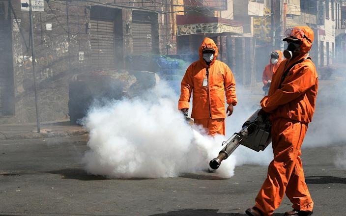 Municipal officials fumigate a street amid a stringent weekend quarantine in Cochabamba to try to halt a surge in infections - Jorge Ábrego/EPA-EFE/Shutterstock