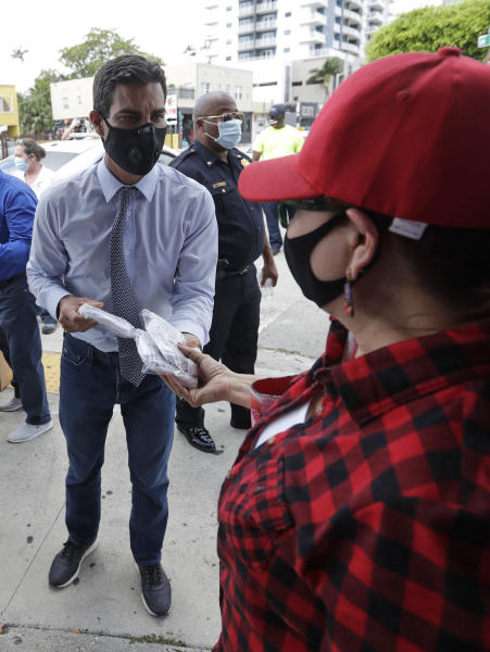 Miami Mayor Francis Suarez, rear, hands out masks to prevent the spread of the new coronavirus, at a mask distribution event, Friday, June 26, 2020, in a COVID-19 hotspot of the Little Havana neighborhood of Miami. Florida banned alcohol consumption at its bars Friday as its daily confirmed coronavirus cases neared 9,000, a new record that is almost double the previous mark set just two days ago. (AP Photo/Wilfredo Lee)