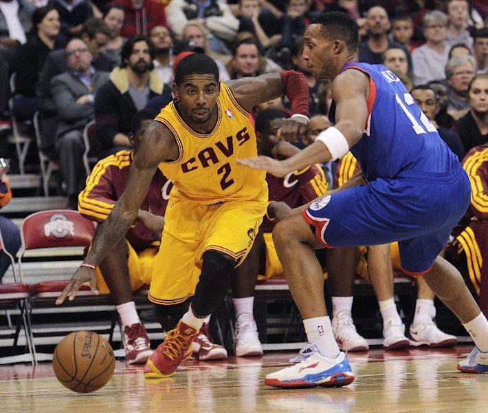 Cleveland Cavaliers' Kyrie Irving, left, drives the baseline against Philadelphia 76ers' Evan Turner during the third quarter of an NBA preseason basketball game Monday, Oct. 21, 2013, in Columbus, Ohio. The Cavaliers beat the 76ers 104-93. (AP Photo/Jay LaPrete)