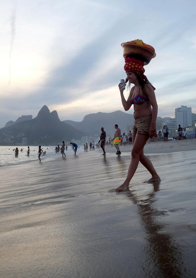 RIO DE JANEIRO, BRAZIL - MARCH 04: A reveler walks on Ipanema Beach during the Banda de Ipanema street carnival bloco on March 4, 2014 in Rio de Janeiro, Brazil. Carnival is the grandest holiday in Brazil, annually drawing millions in raucous celebrations. (Photo by Mario Tama/Getty Images)