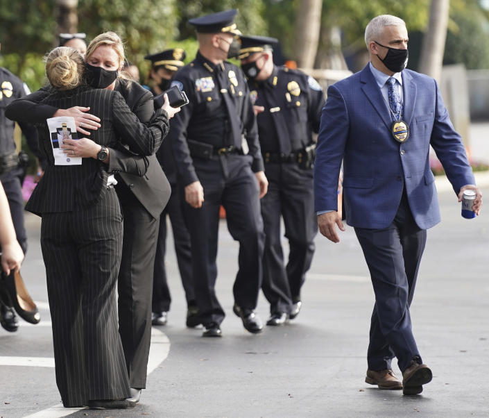 Law enforcement representatives embrace as they leave a memorial service for Special Agent Laura Schwartzenberger, Saturday, Feb. 6, 2021, in Miami Gardens, Fla. Schwartzenberger and Special Agent Daniel Alfin were killed while serving a warrant this week in Sunrise, Fla. (AP Photo/Hans Deryk)