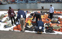 Members of the Indonesian National Transportation Safety Committee (KNKT) and U.S. National Transportation Safety Board (NTSB) investigators team inspect debris found in the waters around the location where a Sriwijaya Air passenger jet crashed, at the search and rescue command center at Tanjung Priok Port in Jakarta, Indonesia, Saturday, Jan. 16, 2021. (AP Photo/Achmad Ibrahim)