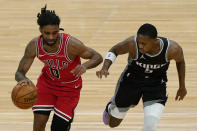 Chicago Bulls guard Coby White, left, drives against Sacramento Kings guard De'Aaron Fox during the first half of an NBA basketball game in Chicago, Saturday, Feb. 20, 2021. (AP Photo/Nam Y. Huh)