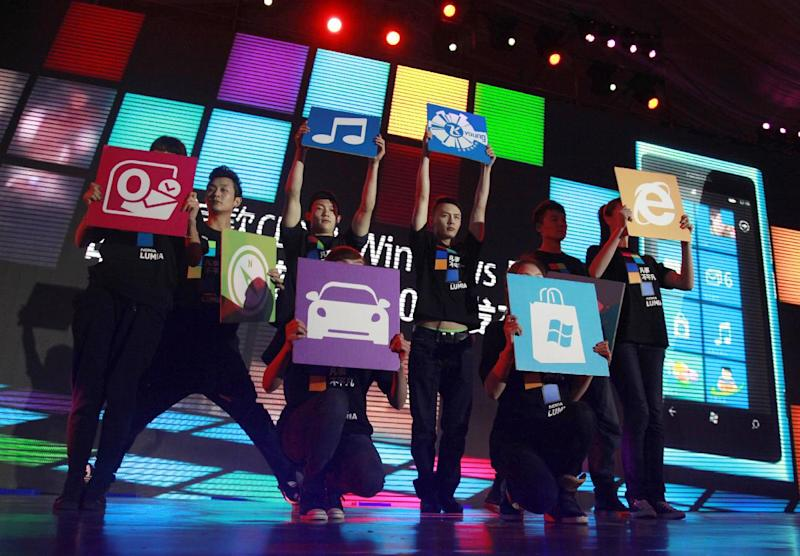 In this March 28, 2012 photo, Chinese performers hold up cards showing the various apps available for online users for shopping and other services at the launch of a mobile phone in Beijing, China. Alibaba, the e-commerce giant planning a blockbuster share sale in the U.S., shook up China's vast but sleepy retailing industry by popularizing online shopping a decade ago. Now it and China's other Internet giants are mounting challenges in areas from banking to broadcasting as smartphones bring even more people online. (AP Photo/Ng Han Guan)