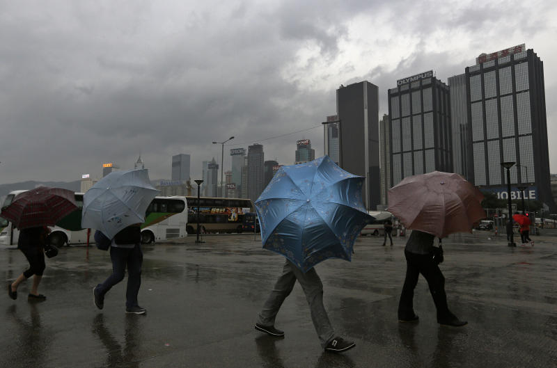 Tourists from mainland China brave strong wind near the waterfront in Hong Kong Sunday, Sept. 22, 2013.The year's most powerful typhoon had Hong Kong in its crosshairs on Sunday after sweeping past the Philippines and Taiwan and pummeling island communities with heavy rains and fierce winds. Typhoon Usagi was grinding westward and expected to make landfall close to Hong Kong late Sunday or early Monday. (AP Photo/Vincent Yu)